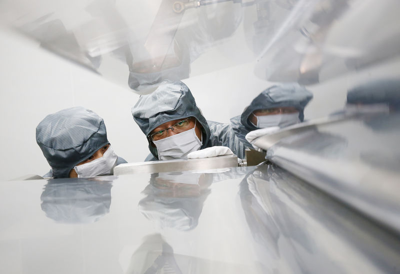 © Reuters. Employees are seen working on a production line of a factory manufacturing composite material products in Nantong