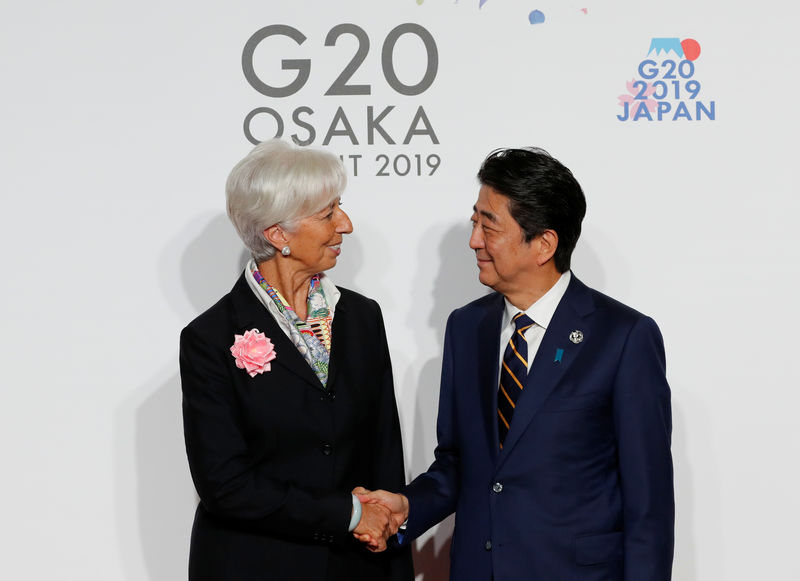 © Reuters. International Monetary Fund (IMF) Managing Director Christine Lagarde is welcomed by Japanese Prime Minister Shinzo Abe upon her arrival for a welcome and family photo session at G20 leaders summit in Osaka