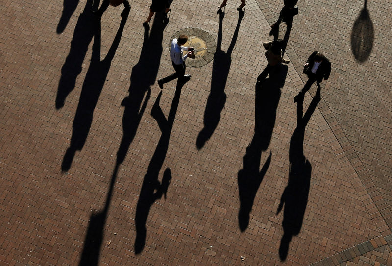 © Reuters. FILE PHOTO:  Commuters cast their shadows as they arrive at the Central Business District during the morning rush hour in Sydney