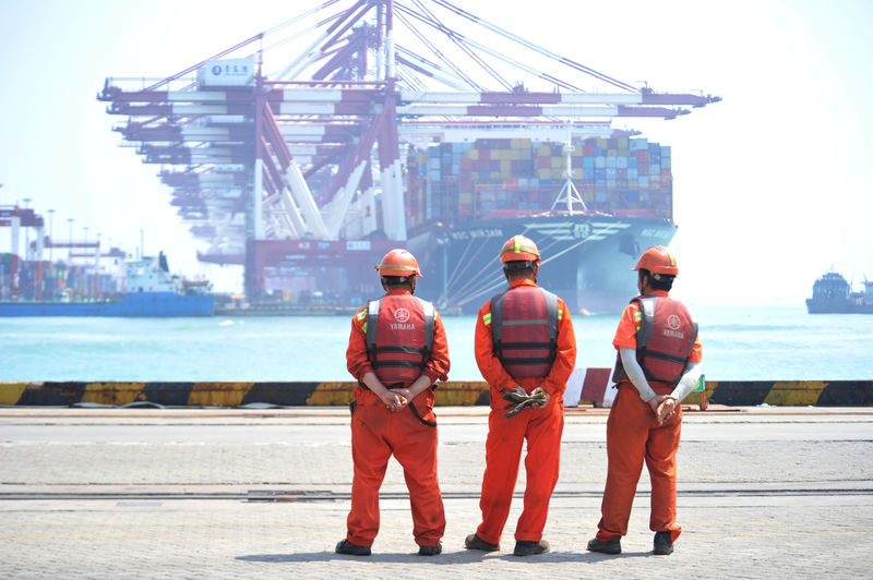 © Reuters. Workers stand at the port of Qingdao, Shandong