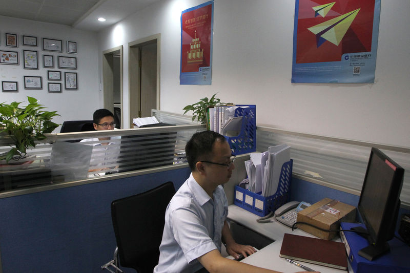 © Reuters. Bank employees, at the small business lending department of CCB, work in front of their computers at the bank's Dongguan branch office