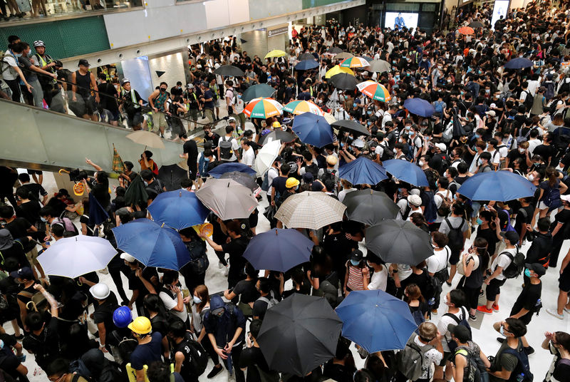© Reuters. FILE PHOTO:  Pro-democracy protesters hold umbrellas inside a mall as they face riot police after a march at Sha Tin District of East New Territories, Hong Kong