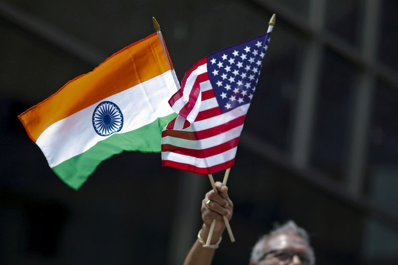© Reuters. FILE PHOTO: Man holds the flags while people take part in the 35th India Day Parade in New York