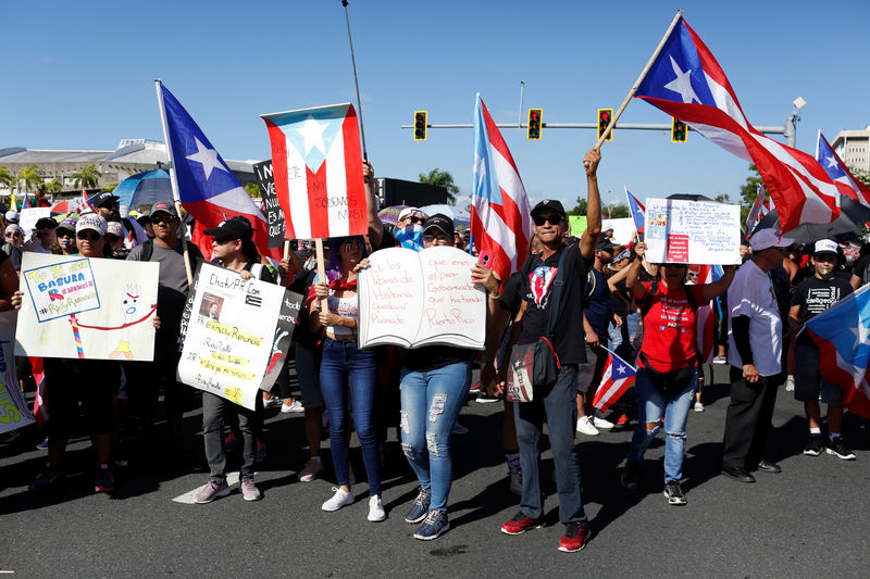 © Reuters. People chant slogans as they wave Puerto Rican flags during ongoing protests calling for the resignation of Governor Ricardo Rossello in San Juan
