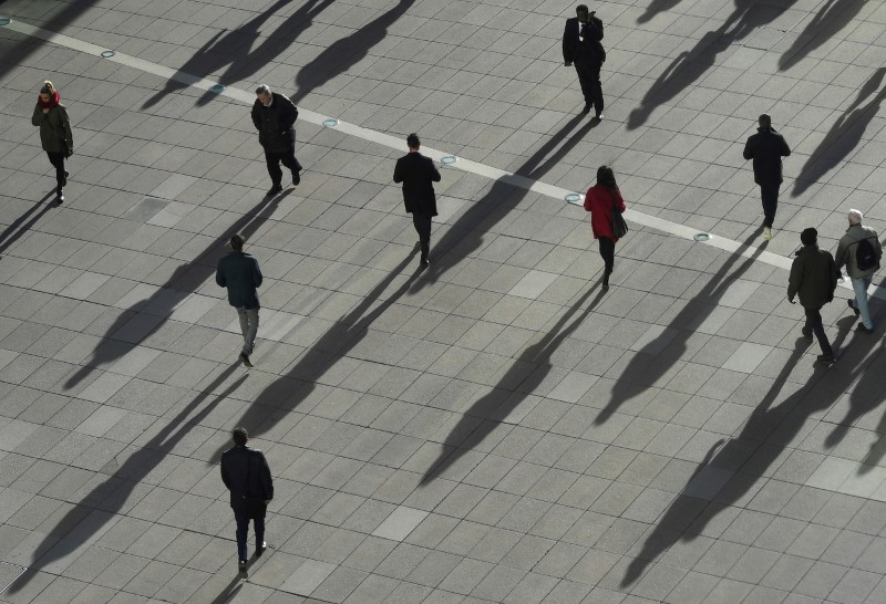 © Reuters. FILE PHOTO: People cast long shadows in the winter sunlight as they walk across a plaza in the Canary Wharf financial district of London