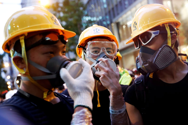 © Reuters. FILE PHOTO: Protesters protect themselves with helmets and masks during a demonstration in Hong Kong