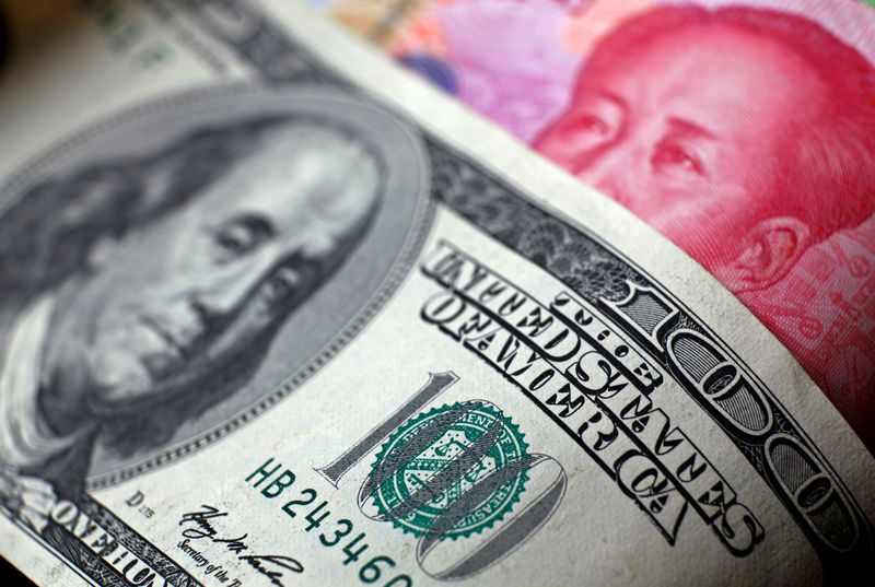 © Reuters. FILE PHOTO: File photo of a Chinese 100 yuan banknote being placed under a $100 banknote in this photo illustration taken in Beijing